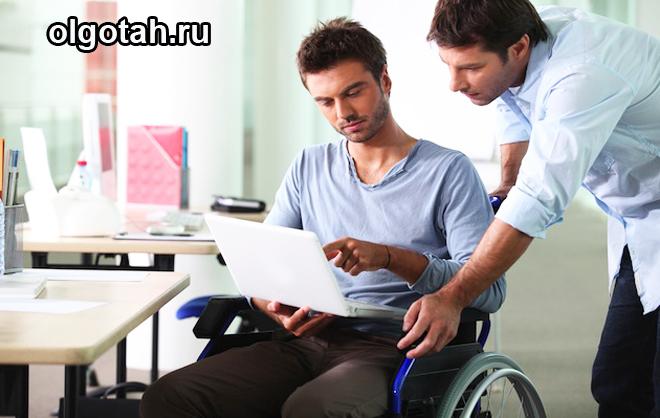 Инвалид в кресле разговаривает с человеком