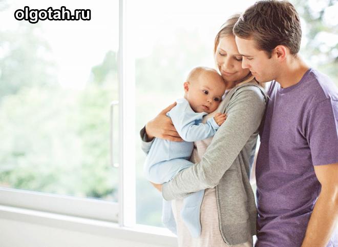 Семья с ребенком стоит у окна