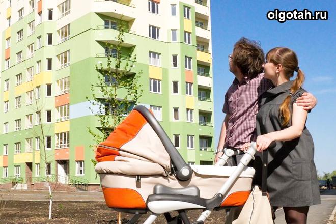 Молодая семья с коляской смотрит на дом
