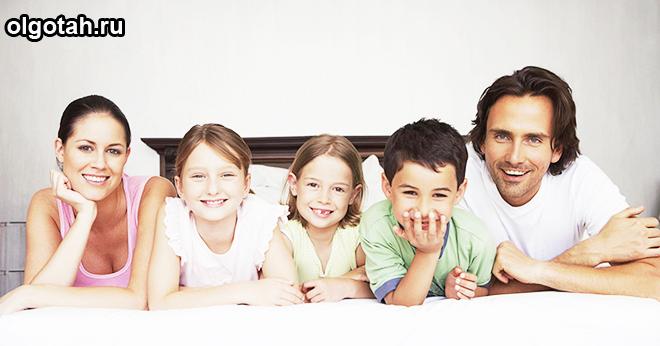 Семья из пяти человек лежит на кровати