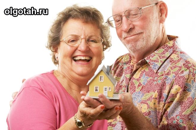 Пожилые мужчина и женщина держат игрушечный домик