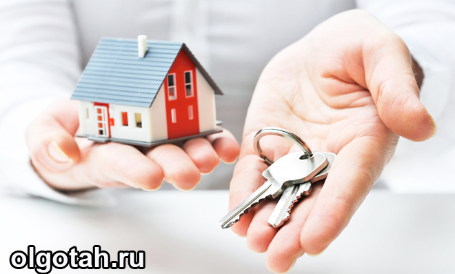 Человек держит в одной руке игрушечный домик, а в другой - ключи