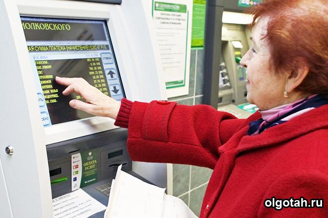 Пенсионерка оплачивает платежки около банкомата