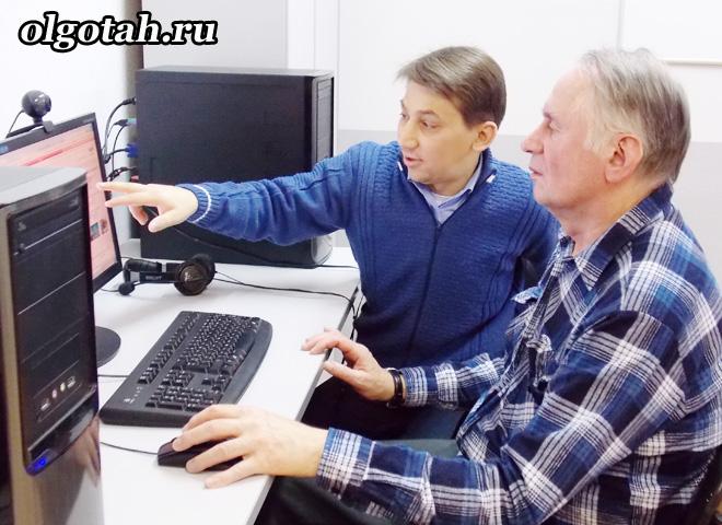 Двое мужчин сидят и смотрят в компьютер