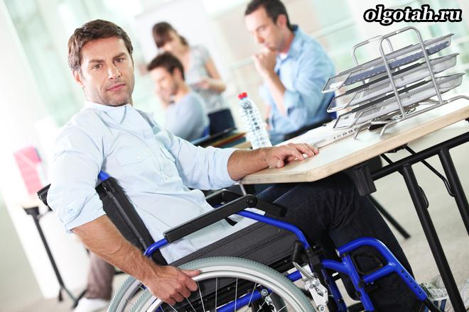 Мужчина-инвалид в офисе, на работе