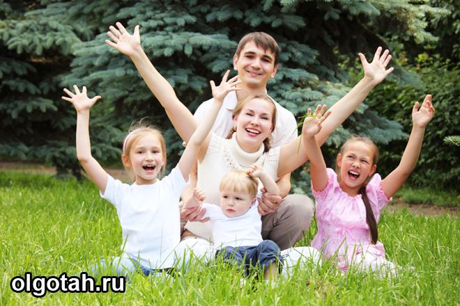 Семья сидит на лужайке, подняв руки вверх