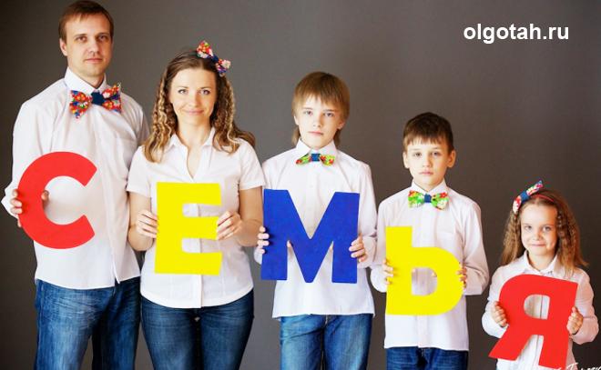 Семья из пяти человек держит буквы