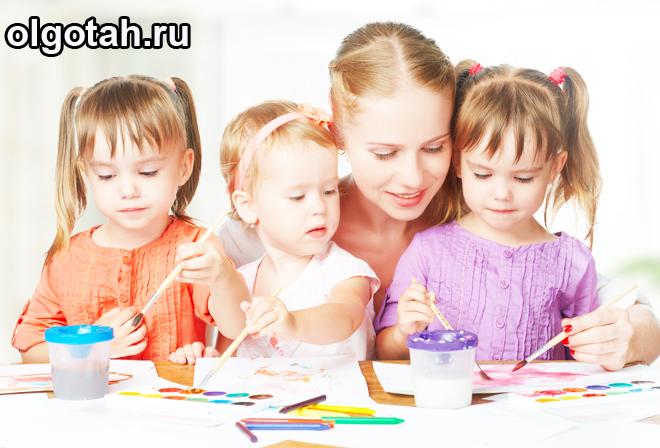 Девушка и три ребенка рисуют в альбоме