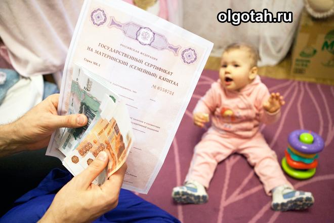 Девушка держит в руках материнский капитал и деньги