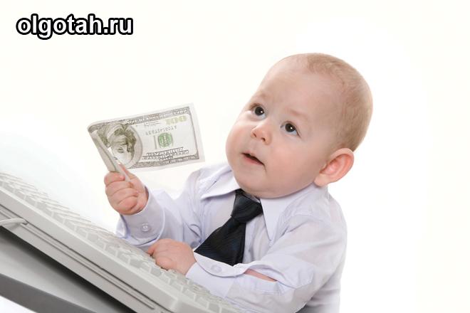Маленький ребенок в костюмчике держит денежку