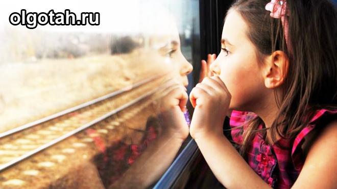 Ребенок смотрит в окно на железную дорогу