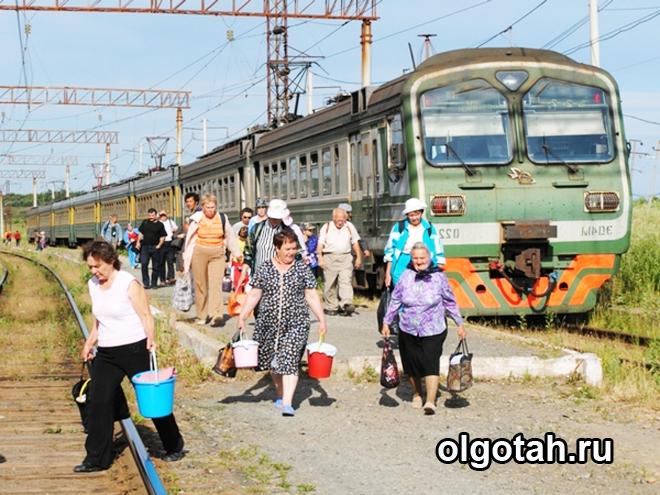 Пассажиры идут с электрички