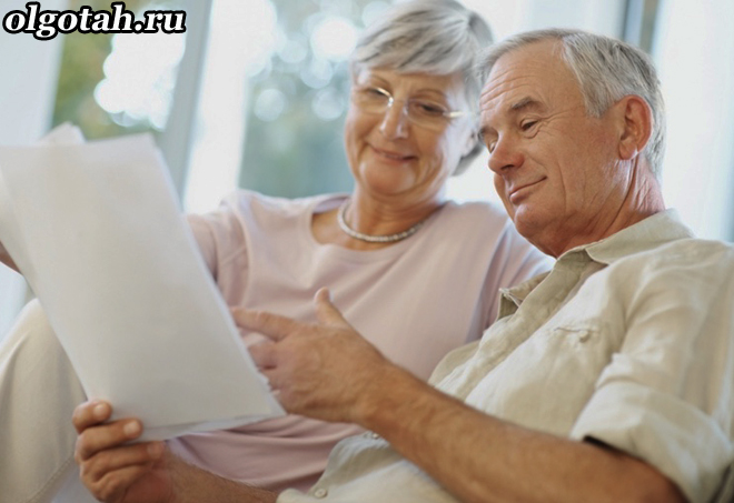 Семья пенсионеров читает бумагу вместе
