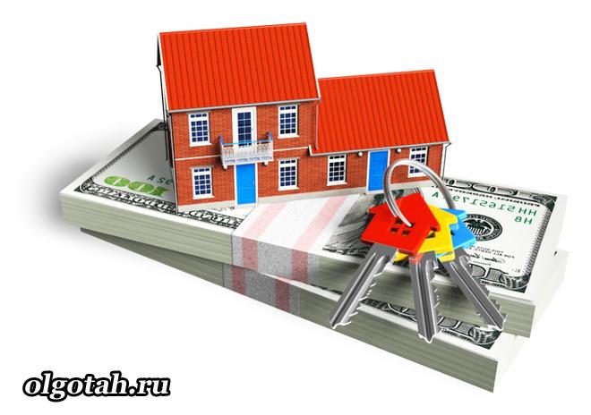 Игрушечный домик стоит на денежных купюрах, рядом ключи