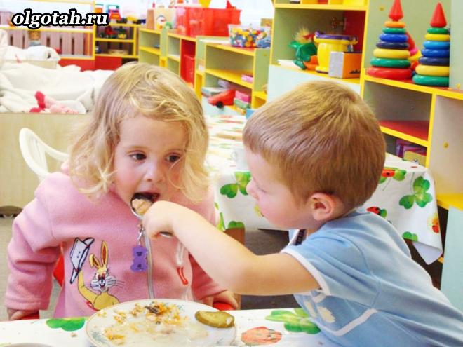 Мальчик кормит девочку с ложки в детском саду
