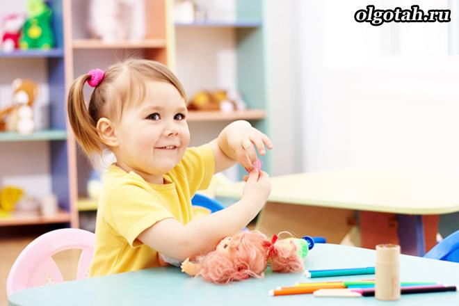 Маленькая девочка сидит за столом