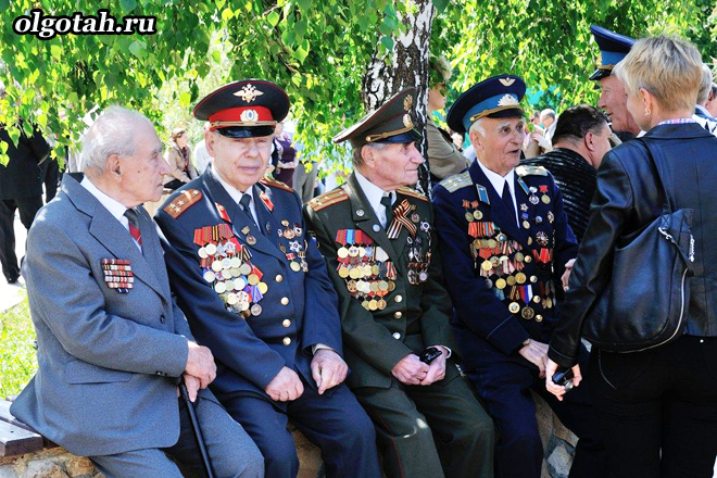 Ветераны с медалями сидят на лавочке