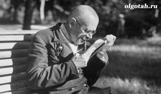 Мужчина читает на лавочке
