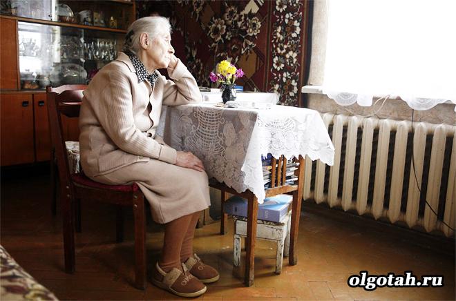 Бабушка сидит в квартире за столом