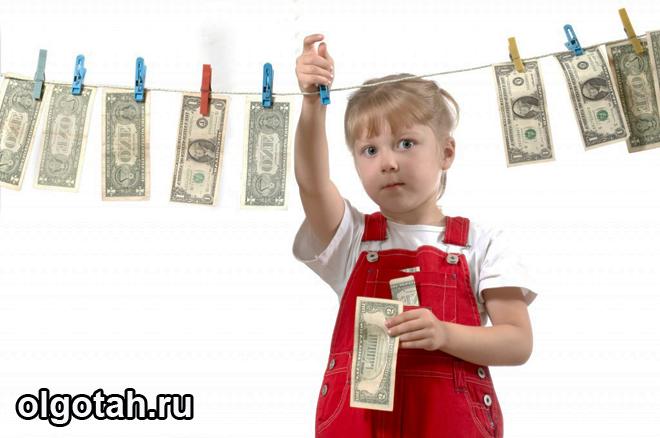 Девочка развешивает деньги на веревке