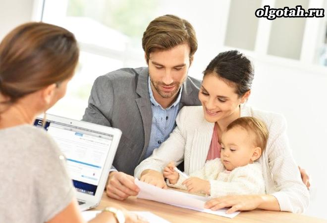 Женщина сидит за ноутбуком, рядом семья