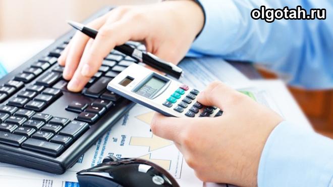 Мужчина считает на калькуляторе, рядом компьютерная клавиатура