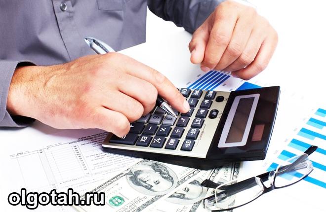 Человек ведет расчеты на калькуляторе, рядом бумажные деньги