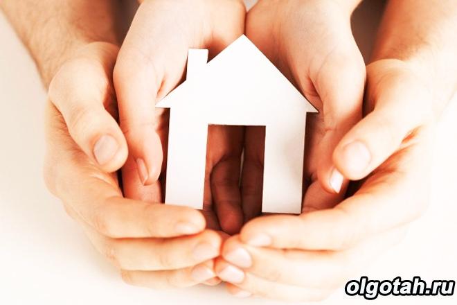 Человеческие руки держат игрушечный домик