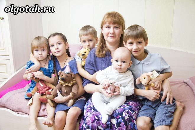 Многодетная мама сидит на диване со своими детьми