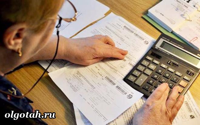Женщина в очках считает на калькуляторе