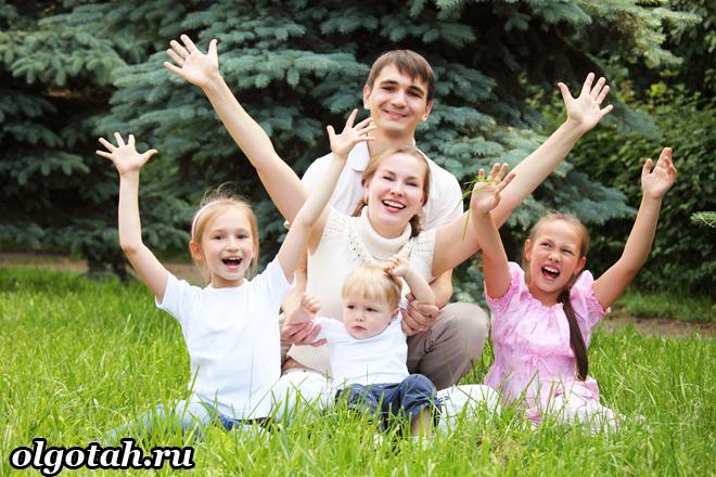 Многодетная семья сидит на лужайки, все подняли руки вверх