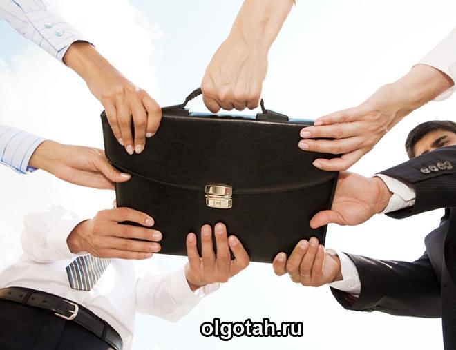 Мужчины в костюмах делят портфель