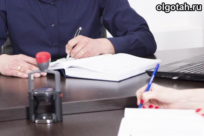 Люди пишут ручкой на бумаге