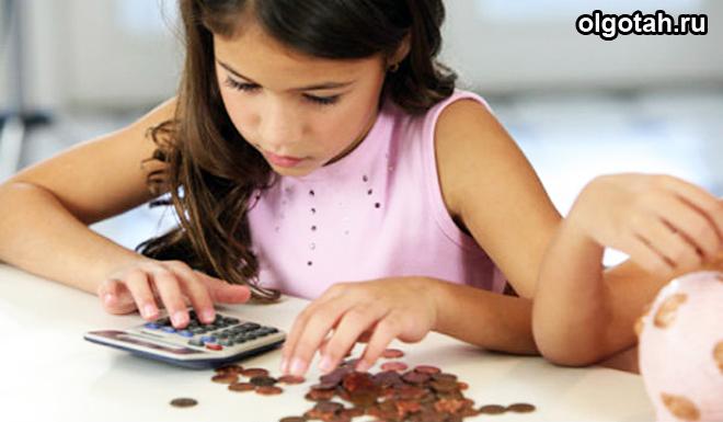 Девочка считает на калькуляторе деньги