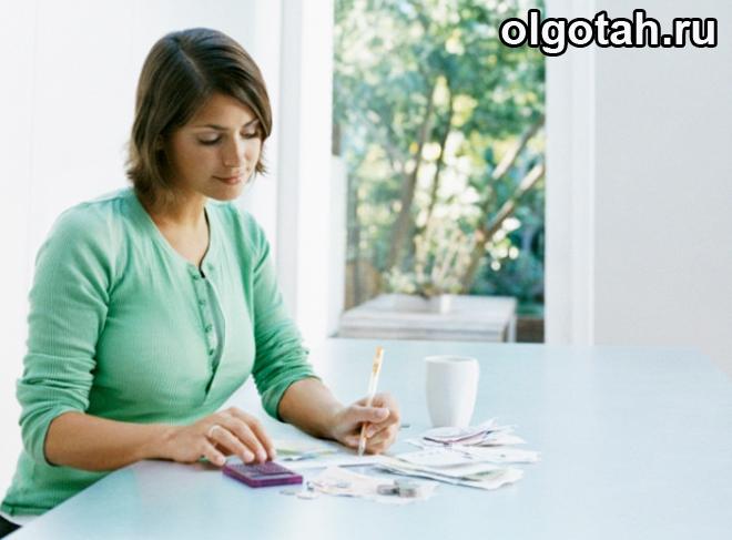 Девушка сидит за столом, заполняет бумаги