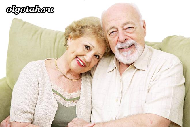 Пожилая пара сидит на диване