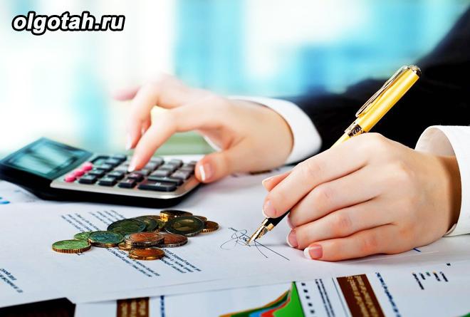 Человек считает на калькуляторе, рядом бумаги и монеты