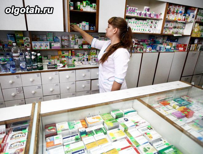 Фармацевт раскладывает лекарства в аптеке