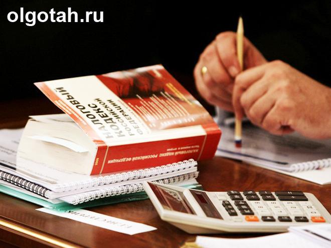 Расчет на калькуляторе, рядом налоговый кодекс