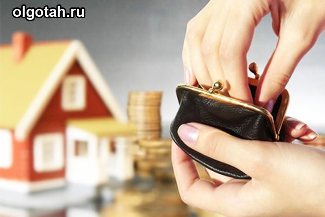 Человек достает монеты из кошелька, на дальнем фоне игрушечный домик