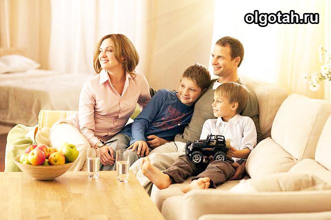 Молодая семья из 4 человек сидит на диване