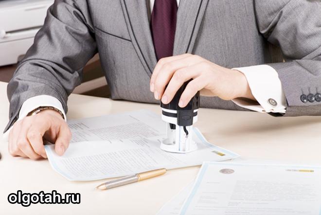 Мужчина ставит печать на документе