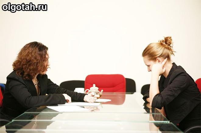 Две женщины сидят за столом переговоров