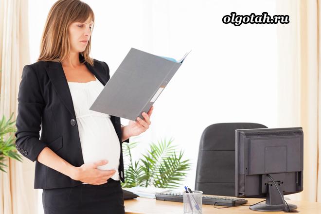 Беременная женщина смотрит в папку с бумагами