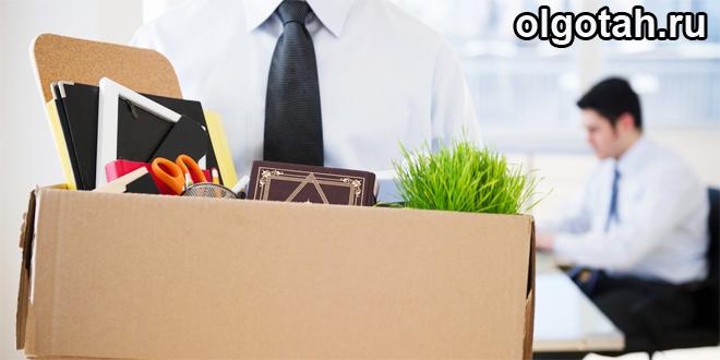 Человек в костюме несет коробку со своими вещами
