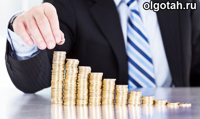 Человек складывает лесенкой золотые монеты