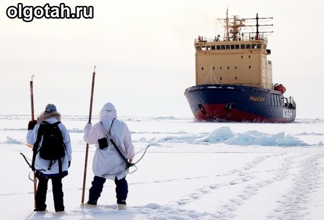 Рабочие идут по льду к кораблю