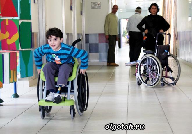 Ребенок-инвалид едет в коляске по коридору