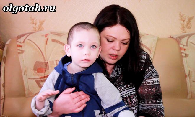 Мама сидит с ребенком инвалидом на диване