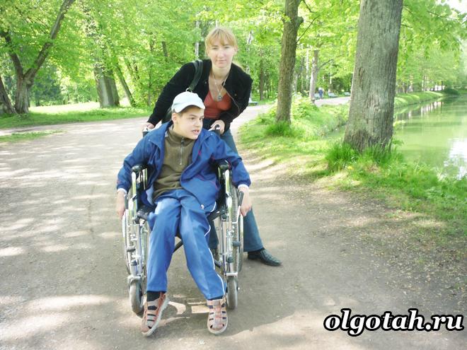 Мама гуляет в парке с ребенком-инвалидом